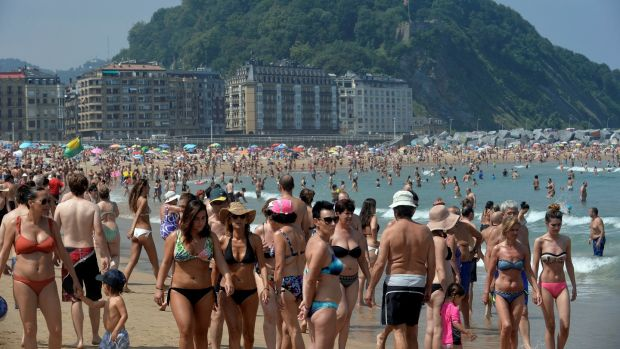 Beachgoers walk on Zurriola beach in the Basque coastal town of San Sebastian, northern Spain. Photograph: Reuters