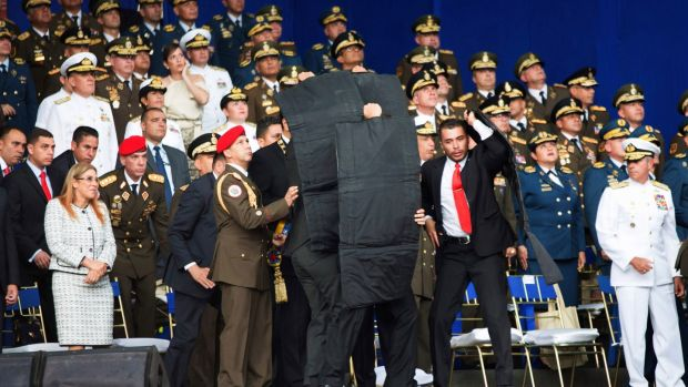 In this photo released by China's Xinhua News Agency, security personnel with shielding surround Venezuela's President Nicolas Maduro during an incident as he gave a speech in Caracas, Venezuela, on Saturday. Photograph: Xinhua/AP