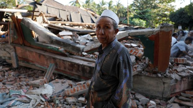 A villager walks through a collapsed house after an earthquake hit Lombok Island in Indonesia. Photograph: Beawiharta/Reuters