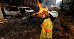 Firefighters help to put out a forest fire in the village of Monchique, Portugal  on Monday. Photograph: Rafael Marchante/Reuters