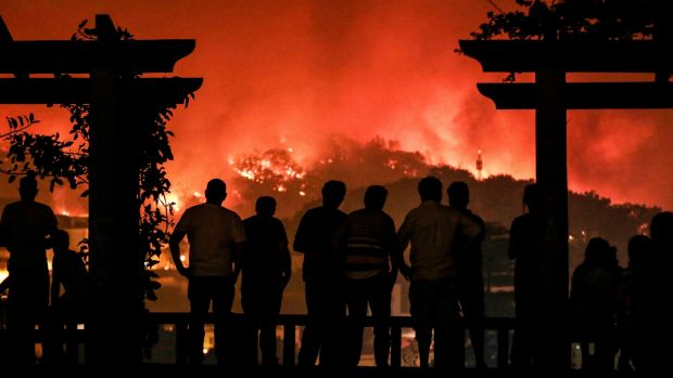 People watch as a forest fire burns on a hill in Monchique, Portugal, on Sunday. Photograph: Filipe Farinha/EPA