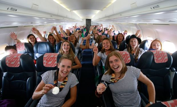 TOP-FLIGHT: The Irish hockey team prepares to return home on a Cityjet flight from London after their unprecedented silver medal finish at the Hockey World Cup in London. Nicci Daly (left) and Katie Mullan show off their medals in front. Photograph: Nick Bradshaw