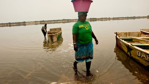 A Senegalese woman carry a heavy load of salt on to the shore at Lac Rose. Photograph: Lar Boland