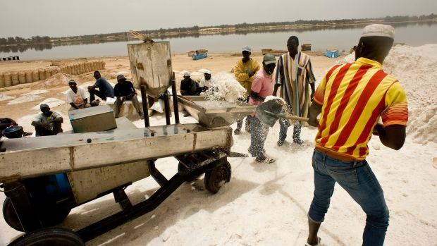 Workers shovel salt into a customised iodisation machine at Lac Rose, Senegal. Photograph: Lar Boland
