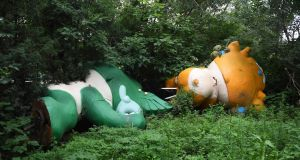 Nini (L) and Yingying, two of the five mascots for the 2008 Beijing Olympic Games, lying among trees behind an abandoned, never-completed mall in Beijing.  A decade after the city hosted the 2008 Olympics, its legacy remains unmistakable. For better or worse, the Games changed the face of Beijing: from the iconic Bird's Nest stadium to the blocks of ancient homes bulldozed in an Olympic building frenzy.  Photograph: AFP PHOTO / GREG BAKER