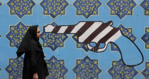 An Iranian woman walks by a mural on the wall of the former US embassy in the Iranian capital Tehran. As US President Donald Trump vowed to block those trading with Iran from the US market, the EU stepped up efforts to save the Iran nuclear deal by encouraging its companies to ignore the White House.   Photograph: Atta Kenare/AFP/Getty Images