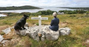 Ann Henning Jocelyn and her Black German Shepherd Pushkin relaxing at the lookout point overlooking her home  with Cashel Bay and the townland of Doonreagan in the backround. Photograph: Joe O'Shaughnessy.