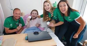 Members of the Ireland women's hockey team, Emily Beatty and Anna O'Flanagan, with head coach Graham Shaw, pictured with Katie Smith (12), Kildare on a visit to  Our Lady's Children's Hospital, Crumlin on Tuesday. Photograph: INPHO/Bryan Keane