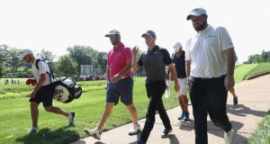 Jon Rahm, Rory McIlroy  and Shane Lowry of Ireland walk off the 12th tee during a practice round prior to the 2018 US PGA Championship at Bellerive Country Club in St Louis, Missouri. Photo: Jamie Squire/Getty Images