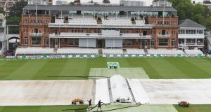 Head groundsman Mick Hunt (bottom right) works on the covers at Lord's. Photograph:  Stu Forster/Getty Images
