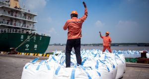 Workers unloading bags of chemicals at a port in Zhangjiagang in China's eastern Jiangsu province. Photograph:  Johannes Eisele/AFP/Getty Images