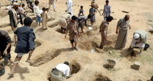 Yemenis dig graves for the victims of a Saudi-led air strike on Thursday that hit a bus carrying children. Photograph: EPA