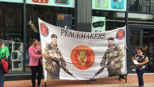 "Up to 40 loyalists held a counterprotest on Royal Avenue against the backdrop of a large UDR-themed banner emblazoned with the words ""Peacemakers""."
