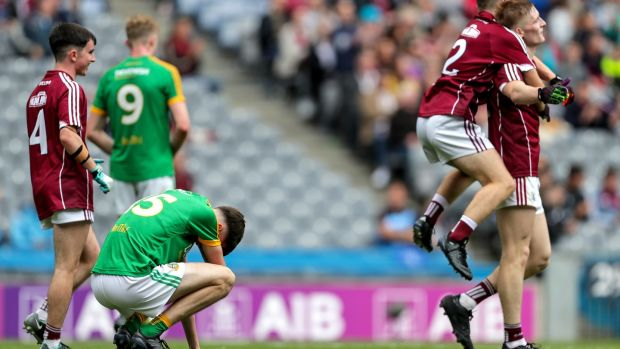 Meath's Luke Mitchell is dejected at the final whistle as Galway players celebrate in the the All-Ireland MFC semi-final against Meath at Croke Park. Photograph: Laszlo Geczo/Inpho