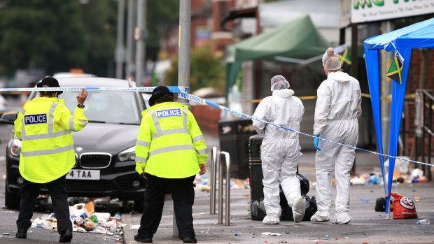 Police officers and forensics at the scene in Claremont Road, Moss Side, Manchester, where several people have been injured after a shooting. Photograph: Peter Byrne/PA Wire