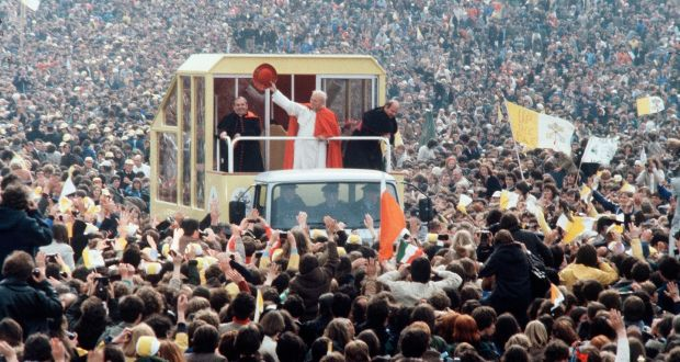 Pope John Paul II waves to cheering crowds from his Popemobile. Running behind schedule, his planned  stop on Séan McDermott Street never happened. Photograph:  Anwar Hussein/ Getty Images