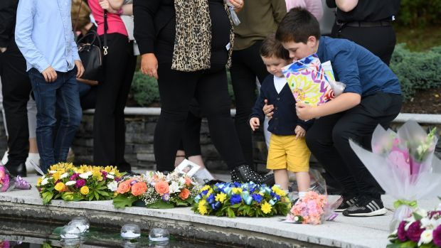 Children leave flowers during a memorial event marking the 20th-anniversary of the Omagh bombing, at the Memorial Garden in Omagh. Photograph: Clodagh Kilcoyne/Reuters