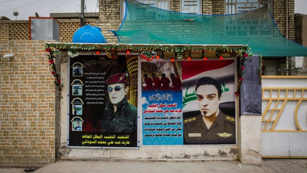 Posters outside the Sudani family home in Baghdad feature larger-than-life photos of Captain Sudani and poems of mourning written by his father. Photograph: Ivor Prickett/The New York Times