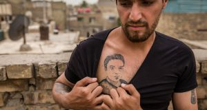 Munther al-Sudani shows off a tattoo of his brother, Captain Harith al-Sudani, in Baghdad. Photograph: Ivor Prickett/The New York Times