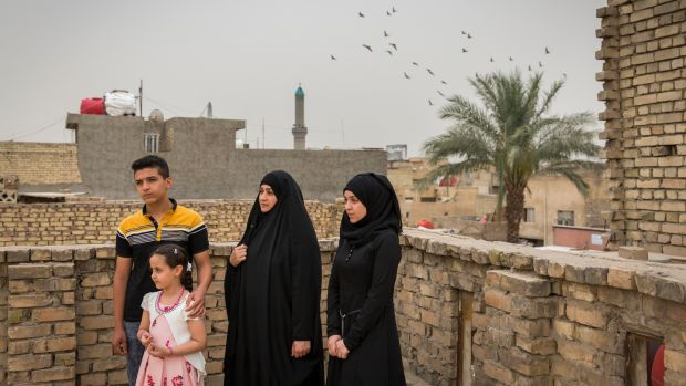 Captain Harith al-Sudani's wife, Raghad Hasan Chaloob, centre, and their three children, Riyam, Rawan and Muamal on the roof of their home in Baghdad. Photograph: Ivor Prickett/The New York Times