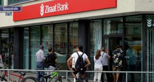 Customers stand in queue outside the Turkish Ziraat Bank branch in Frankfurt, Germany