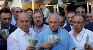 Turkish businessmen heed a call to sell dollar and euro savings in support of the lira. Photograph: Umit Bektas/Reuters