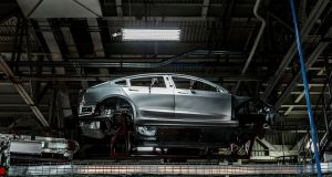 A Tesla Model 3 on the body line at the company's factory in California. Photograph: Hemm Klok/New York Times