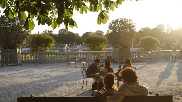 Visitors bask in the sun at the Luxembourg Gardens in Paris. Photograph: Ed Alcock/The New York Times