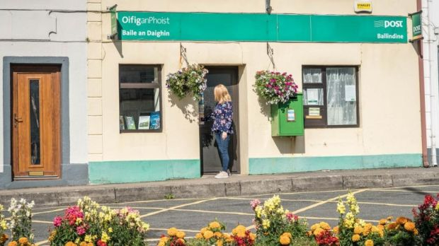 Postmistress Ann Gilmore closes the door of Ballindine post office at the end of its last day of business. Photograph: Keith Heneghan