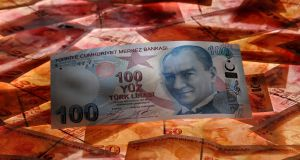 A 100 Turkish lira banknote is seen on top of 50 Turkish lira notes
