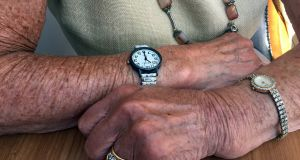 Rosie, age 88, is tanned from sunbathing in her front garden. She wears two watches. Her late husband gave her the jewelled watch and rings. Her daughter gave her the other watch, with large numerals so she can read the time