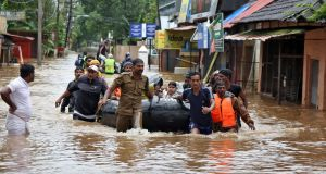 Rescuers take people from a flooded area to a safer place in Aluva in the southern state of Kerala, India. Photograph: Sivaram V/Reuters