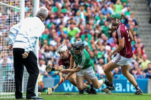 Galway's Daithí Burke is unable to stop Graeme Mulcahy of Limerick scoring a goal. Photograph: Ryan Byrne/Inpho