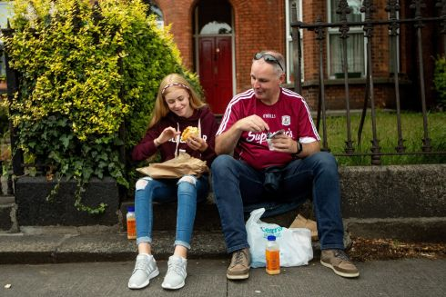 Ava and her father Jim Collins from Loughrea have something to eat before the game. Photograph: James Crombie/Inpho