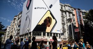 People cross an Istanbul street beneath a billboard advertising the Apple iPhone X. President Erdogan has indicated that Turkey will boycott US electronic goods, including Apple products. Photograph: Getty Images