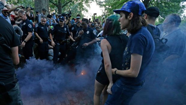 Police and protesters react to a smoke bomb during a rally to remove the confederate statue known as Silent Sam from campus at the University of North Carolina. Photograph: Gerry Broome/AP