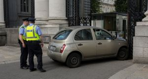 Gardaí at the scene of a collision where a car crashed into the gates of Government Buildings in Dublin. Photograph: Collins