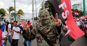A masked pro-government supporter takes part in a march in support of Nicaraguan president Daniel Ortega in Managua on August 18th. Photograph: Oswaldo Rivas/Reuters