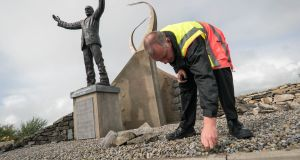 Noel Jennings, fire and security duty officer at Ireland West Airport Knock, pulling weeds beside the statue of Msgr Horan in preparation for the visit of Pope Francis. Photograph: Keith Heneghan