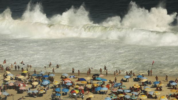 Waves break as people gather on Copacabana beach. Photograph: Mario Tama/Getty Images