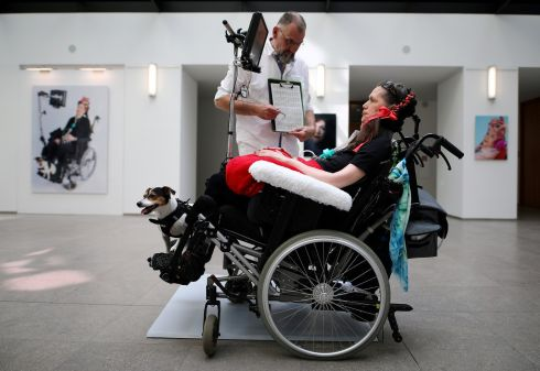 PORTRAIT OF THE ARTIST: Angela Jansen communicates with her carer during her performance 'I'm still present' at an exhibition in Berlin, Germany. Photograph: Hannibal Hanschke/Reuters