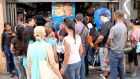 People queue to buy food at a mini market in downtown Caracas, Venezuela. Smurfit's local unit represents less than 1 per cent of core earnings