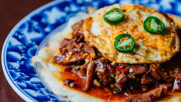 Shredded duck in black bean sauce topped with a fried egg on the brunch menu at Hang Dai