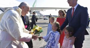 Pope Francis  receiving a bouquet of flowers from a daughter of  Minister for  Foreign Affairs  Simon Coveney  at Dublin airport. Photograph: EPA