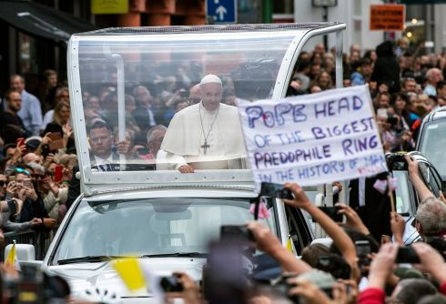 A protester holds up a banner while Pope Francis travels through the streets of Dublin. Photograph: Will Oliver/EPA