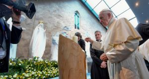 Pope Francis lights a candle as he visits Knock Shrine during his apostolic trip to Ireland on Sunday. Photograph: Ciro Fusco/Pool photo via AP