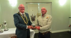 Séamus O'Loughlin (Ennis), winner of ITFFA individual competition on Lough Lene, receiving the Lennon Cup from president, John Deacy
