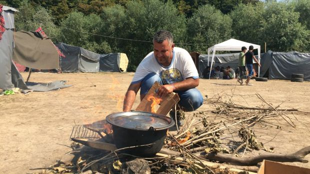 A man cooks at a camp in Velika Kladusa, near Bosnia's border with Croatia, now home to hundreds of migrants. Photograph: Daniel McLaughlin