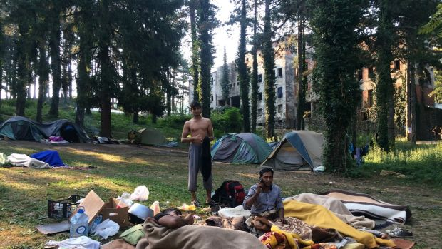 Migrants wake up in a field outside a derelict dormitory in Bihac, northwest Bosnia, which is now home to about 1,000 people. Photograph: Daniel McLaughlin