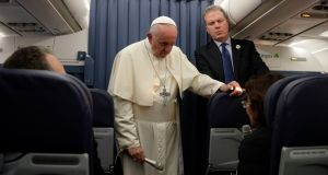 Pope Francis, flanked by Vatican spokesperson Greg Burke, listens to a journalist's question during a press conference aboard of the flight to Rome at the end of his two-day visit to Ireland. Photograph: Gregorio Borgia/AP Photo/Pool